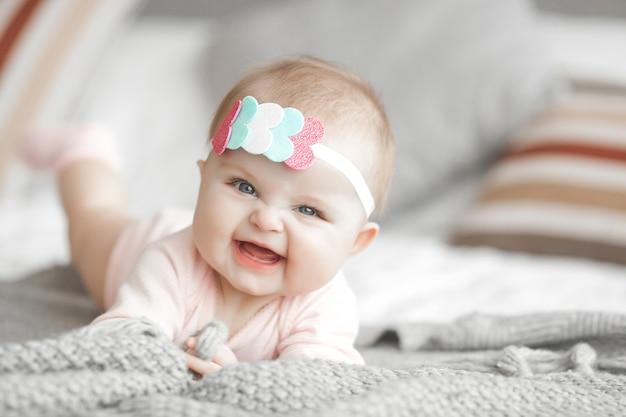 Nettes kleines baby zu hause im schlafzimmer. ein kind drinnen. 6. monat kinderporträt. entzückendes nettes baby.
