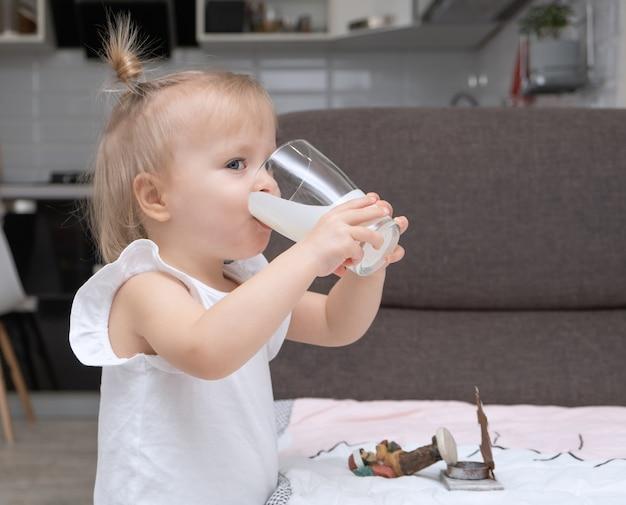 Nettes kleines blondes mädchen, das organische milch trinkt, glas zu hause küche hält