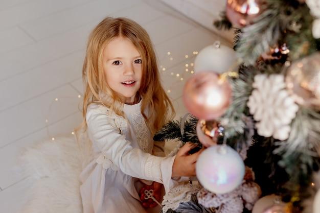 Nettes kleines blondes mädchen im kleid nahe weihnachtsbaum