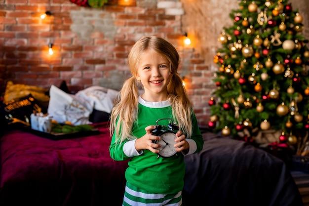Nettes kleines blondes mädchen im schlafanzug nahe weihnachtsbaum
