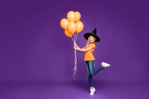Nettes kleines blondes mädchen mit einem hexenhut und luftballons