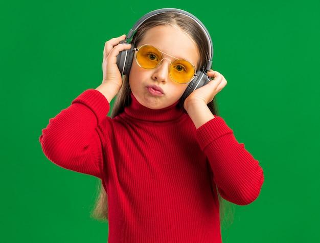 Nettes kleines blondes mädchen mit kopfhörern und sonnenbrille, das kopfhörer greift und auf die kamera schaut, die auf grüner wand isoliert ist?