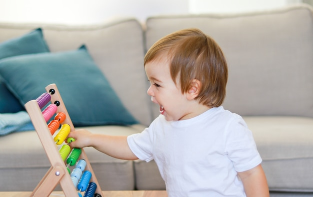 Nettes kleines glückliches baby, das mit buntem abakus spielt. frühes bildungs- und entwicklungskonzept.