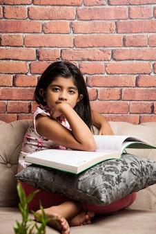 Nettes kleines indisches asiatisches mädchen liest buch beim sitzen auf dem sofa oder der couch zu hause