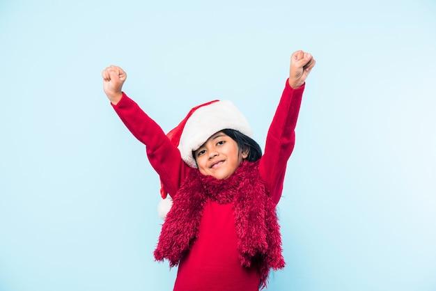 Nettes kleines indisches asiatisches mädchen mit weihnachtsmütze, das weihnachten feiert, während es über einem einfachen hintergrund steht