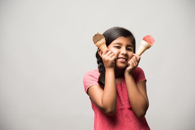 Nettes kleines indisches mädchen, das eiscreme im kegel isst