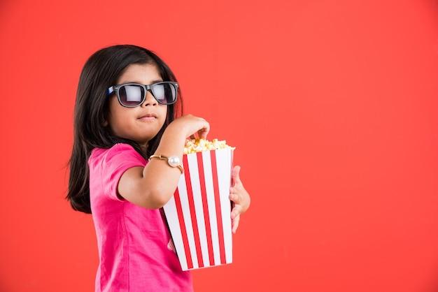 Nettes kleines indisches mädchen, das popcorn isst, während es eine sonnenbrille oder eine 3d-brille in einem theater trägt. stehend über buntem hintergrund isoliert