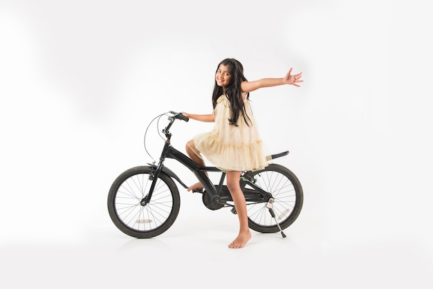Nettes kleines indisches oder asiatisches mädchen, das auf dem fahrrad reitet, isoliert auf weißem hintergrund mit ballons