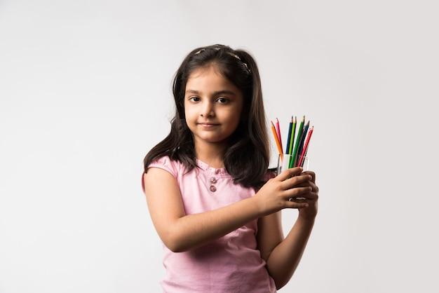 Nettes kleines indisches oder asiatisches mädchen, das buntstifte hält und isoliert auf weißem hintergrund steht