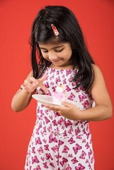 Nettes kleines indisches oder asiatisches mädchen, das ein stück erdbeer- oder schokoladengebäck oder -kuchen in einem teller isst. auf buntem hintergrund isoliert