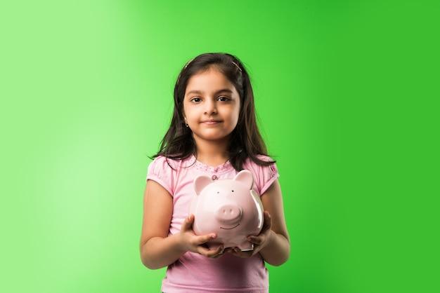 Nettes kleines indisches oder asiatisches mädchen, das rosa sparschwein und bücher hält, während es über grünem hintergrund steht