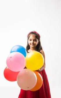 Nettes kleines indisches oder asiatisches mädchen mit bunten luftballons oder gubbare in hindi, über weißem oder rotem hintergrund