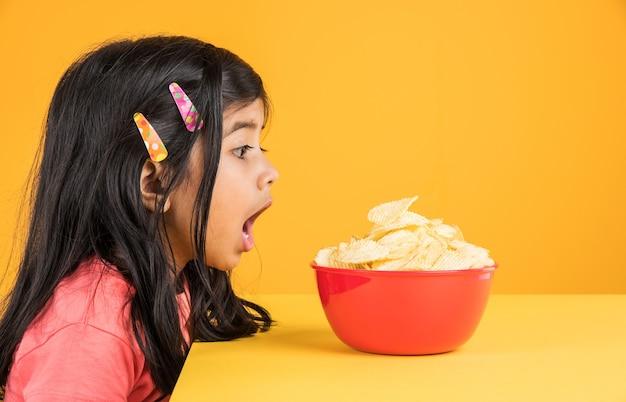 Nettes kleines indisches oder asiatisches mädchenkind, das chips oder kartoffelwaffeln in großer roter schüssel isst, über gelbem hintergrund