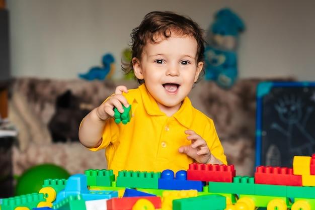 Nettes kleines jungenkind, das zu hause mit bunten würfeln spielt