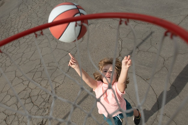 Nettes kleines jungenkind in basketballuniform, das mit basketball für erschossenes glückliches kind springt, das ba ...