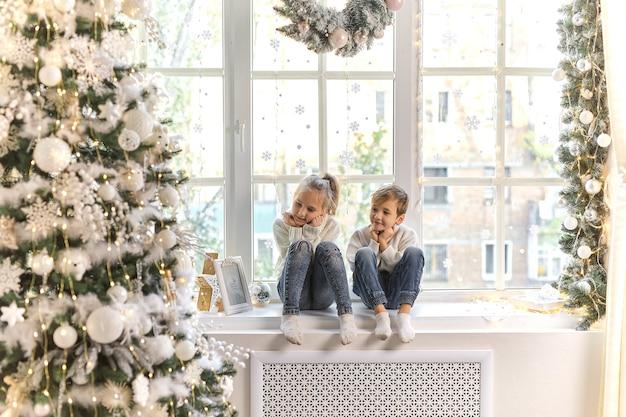 Nettes kleines kind auf der fensterbank zu hause, das auf die weihnachtsfeier wartet