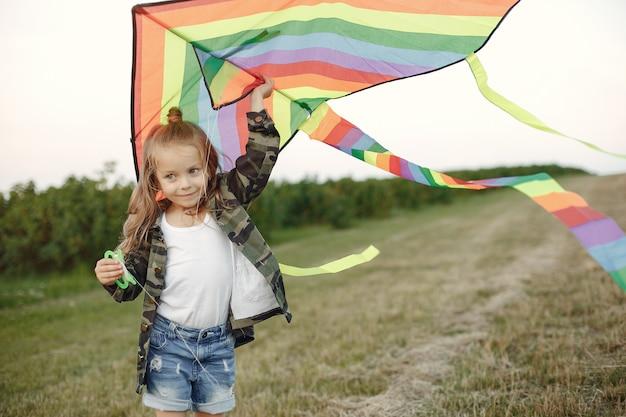 Nettes kleines kind auf einem sommergebiet mit einem drachen