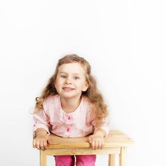 Nettes kleines kind, das auf dem stuhl sitzt und lächelt