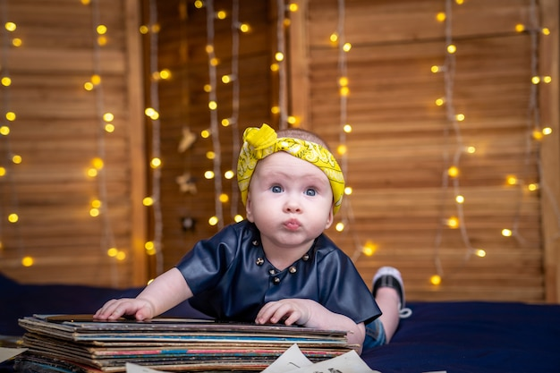 Nettes kleines kind, das auf einem stapel retro-aufzeichnungen liegt. das kind im disco-stil gekleidet