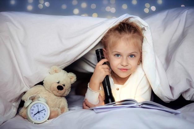 Nettes kleines kind, das ein buch mit einer taschenlampe unter der decke liest