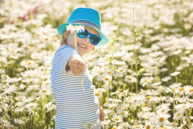Nettes kleines kind, das eine kamillenblume gibt