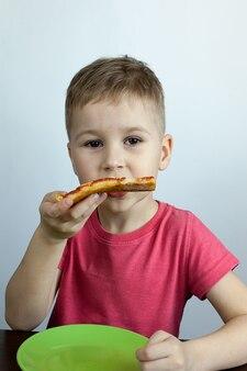 Nettes kleines kind, das einen bissen von einem köstlichen margarita-pizzastück nimmt.