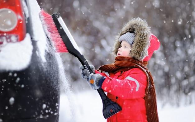 Nettes kleines kind, das hilft, einen schnee von einem auto zu bürsten