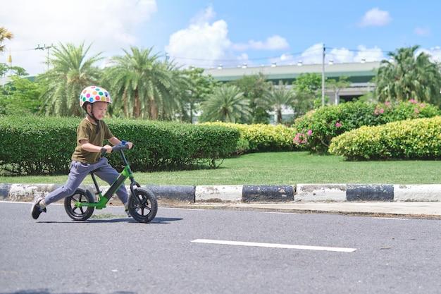 Nettes kleines kind, das schutzhelm trägt, der lernt, erstes laufrad zu fahren