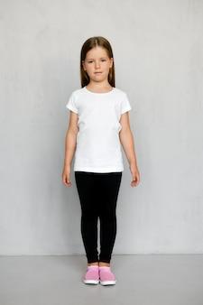 Nettes kleines kind mit langen haaren im weißen t-shirt und in der schwarzen jogginghose, die aufwirft
