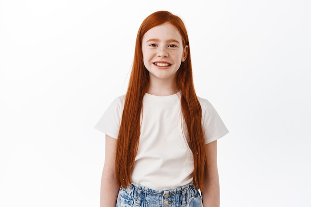 Nettes kleines kind mit langen roten haaren, das vorne lächelt und glücklich aussieht und über weißer wand steht