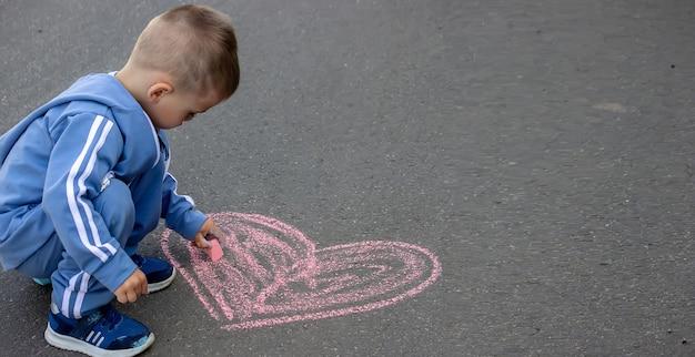 Nettes kleines kind zeichnet draußen mit kreide