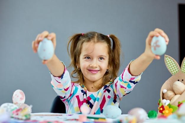 Nettes kleines kindermädchen am ostertag hält osterei in der hand zu hause