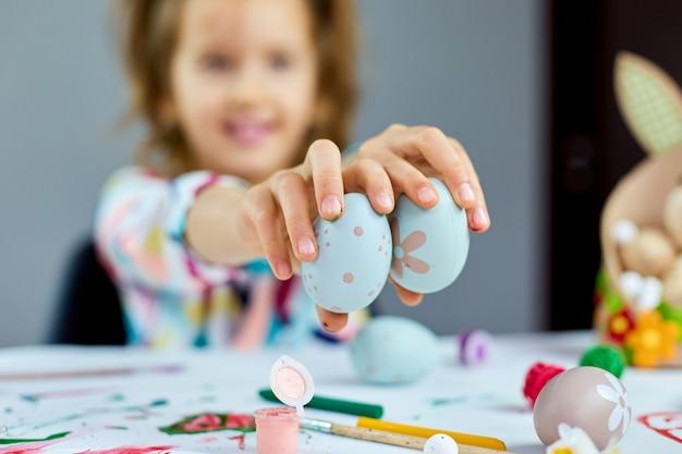Nettes kleines kindermädchen am ostertag hält ostereier in der hand zu hause