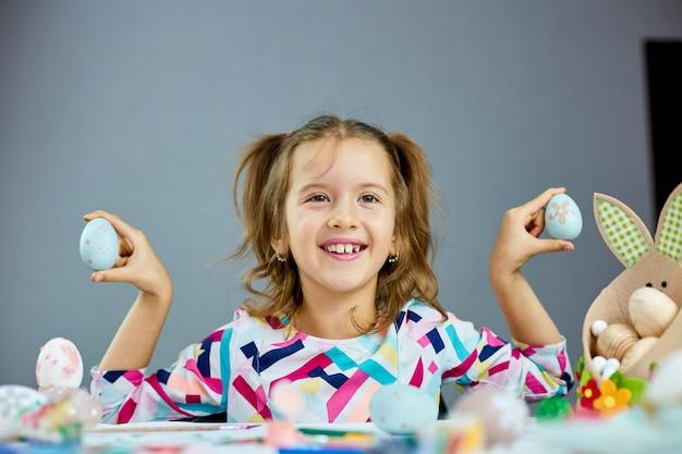 Nettes kleines kindermädchen am ostertag halten osterei in der hand zu hause. mädchen mit gemalten eiern auf hellem hintergrund, glückliches ostern