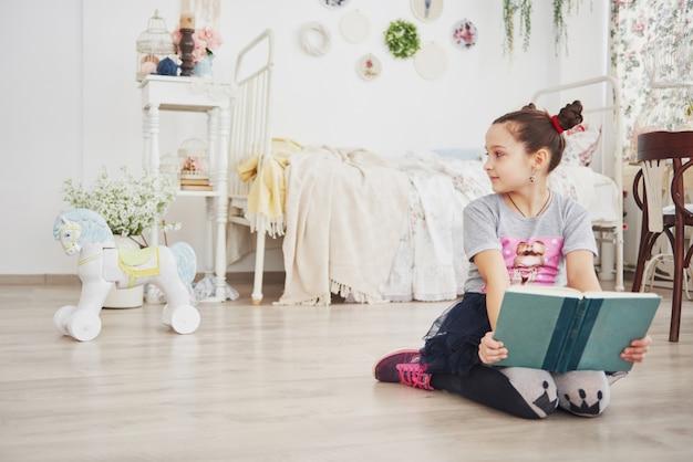 Nettes kleines kindermädchen, das ein buch im schlafzimmer liest. kind mit krone sitzt auf dem bett nahe fenster