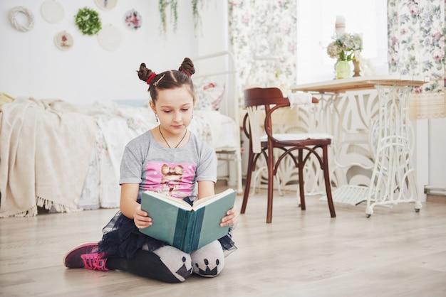 Nettes kleines kindermädchen, das ein buch im schlafzimmer liest. scherzen sie mit der krone, die auf dem bett nahe fenster sitzt