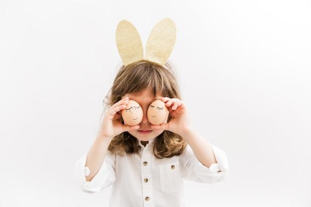 Nettes kleines kindermädchen, das goldene hasenohren trägt und spaß mit eiern hat. osterfeier.