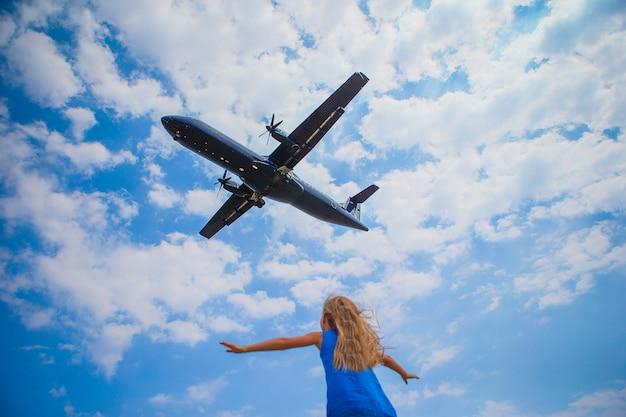 Nettes kleines kindermädchen, das zum himmel schaut und flugzeug direkt über ihr fliegt