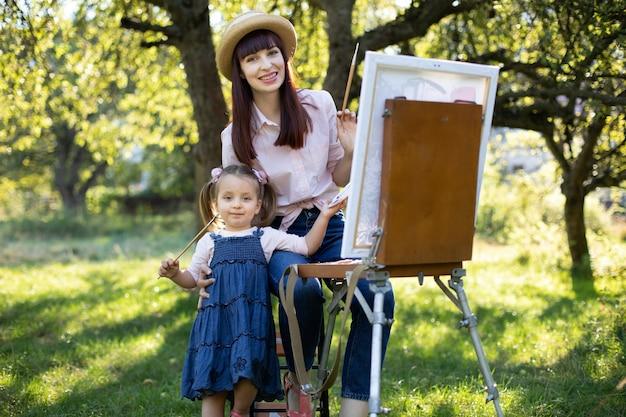 Nettes kleines kindermädchen im sommergarten, hält einen pinsel und malt zusammen mit ihrer mutter ein bild auf leinwand. hübsche junge mama sitzt auf dem stuhl und umarmt das mädchen