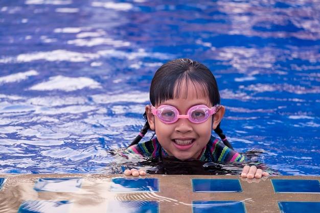 Nettes kleines kindermädchen mit schutzbrille im schwimmbad