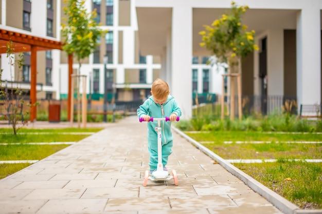 Nettes kleines kleinkindmädchen in blauen overalls, das auf kickroller reitet, glückliches gesundes schönes babykind hat ...