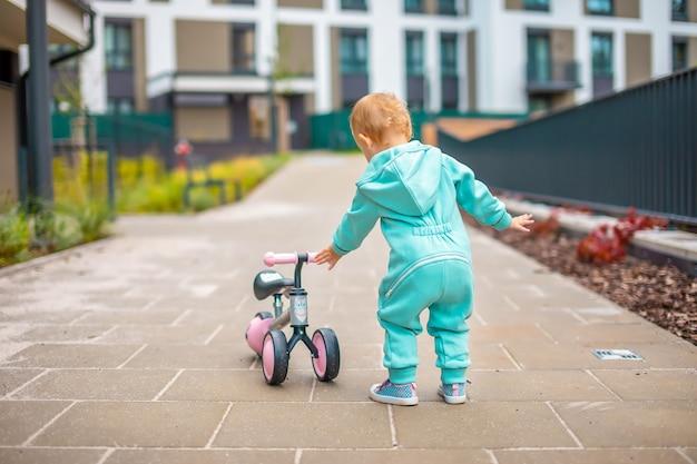 Nettes kleines kleinkindmädchen in blauen overalls, das auf laufrad reitet, glückliches gesundes schönes baby...
