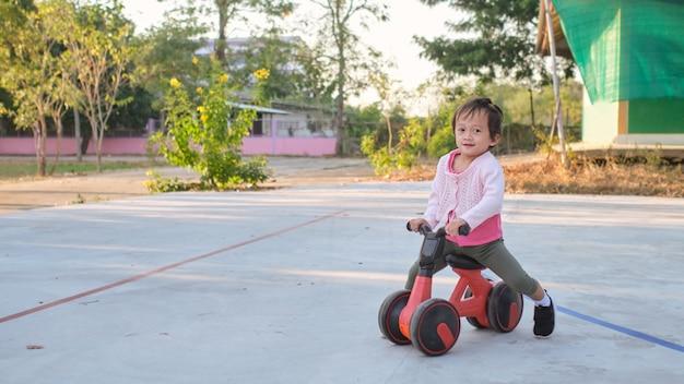 Nettes kleines kleinkindmädchenkind, das lernt, erste laufradkinder zu fahren, die im park radfahren