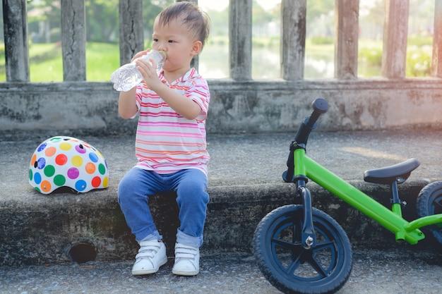 Nettes kleines kluges asiatisches 2 jahre altes kleinkindjungenkind, das eine pause macht und reines wasser von der plastikflasche trinkt, nachdem es sein laufrad (laufrad) im park fährt, kind trinkt wasser nach sport.