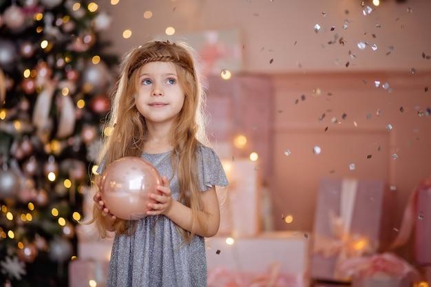 Nettes kleines lachendes blondes mädchen mit langen haaren, die einen weihnachtsball halten