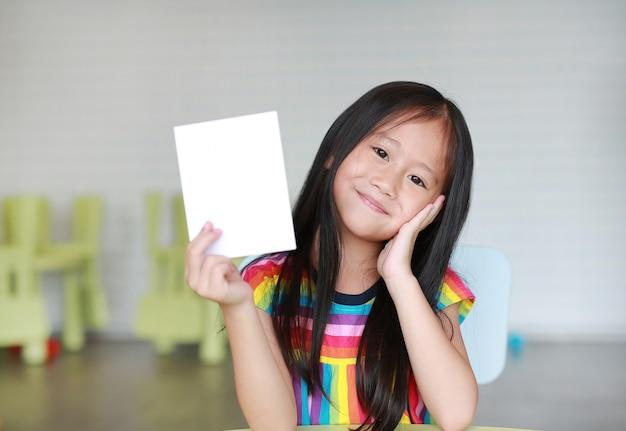 Nettes kleines lächelndes asiatisches kindermädchen, das leere weißbuchkarte in ihrer hand hält