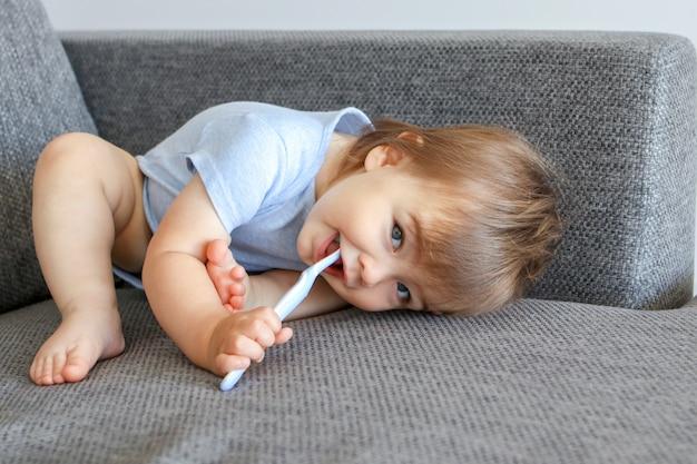 Nettes kleines lächelndes baby mit zahnbürste
