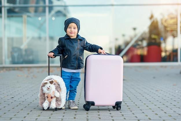 Nettes kleines lächelndes mädchen in der stilvollen freizeitkleidung mit dem lustigen flauschigen koffer im flughafen, der ihre hand winkt.