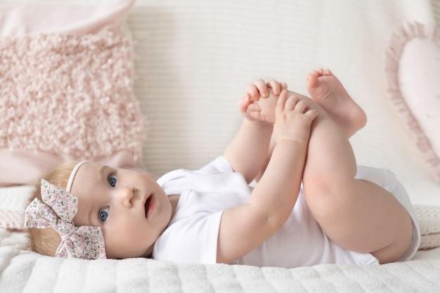 Nettes kleines lustiges kaukasisches blondes baby mit rosa bogen auf kopf liegend ob bett, das mit füßen auf oberfläche der dekorativen kissen zu hause spielt