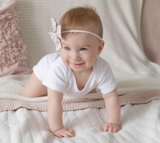 Nettes kleines lustiges kaukasisches blondes baby mit rosa schleife auf kopf, lächelnd, auf vieren auf oberfläche der dekorativen kissen zu hause